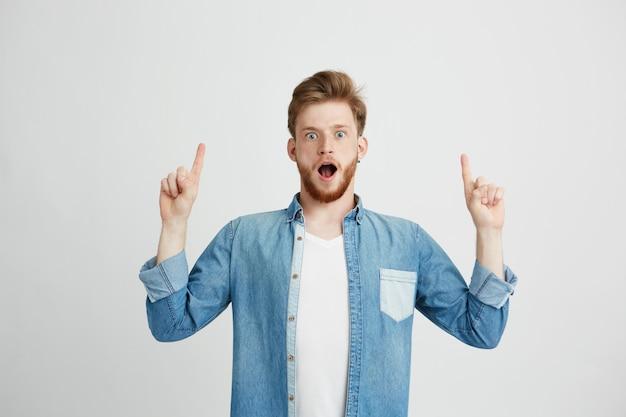 Retrato del hombre hermoso joven sorprendido con la boca abierta que señala el dedo para arriba.