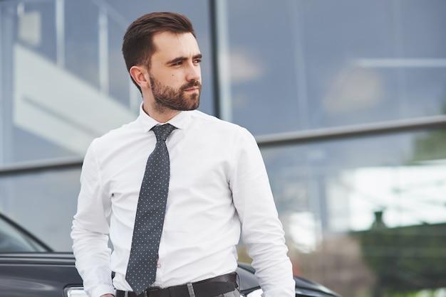 Retrato de un hombre hermoso en ropa de negocios de pie afuera en la oficina.