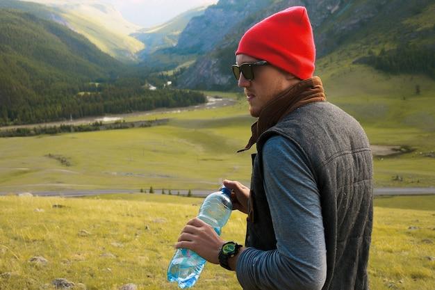 Retrato de hombre hipster viajando a las montañas, usa sombrero rojo y ropa hipster, toma fotos