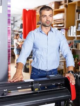 Retrato de un hombre en una impresora en un taller