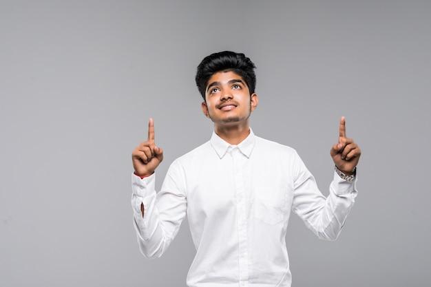 Retrato de hombre indio en camisa apuntando con los dedos hacia arriba sobre la pared blanca