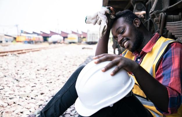 Retrato del hombre de ingeniería de áfrica americano usar casco y relajarse cerca del contenedor de acero antes de trabajar duro en frente del garaje del tren