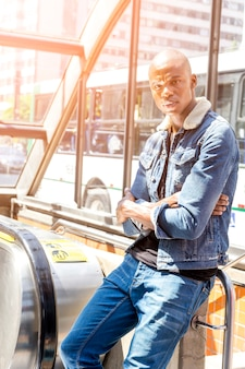 Retrato de un hombre joven africano que se coloca en la entrada del metro que mira lejos