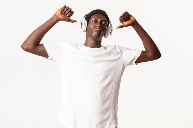 Retrato de hombre joven afroamericano feliz y orgulloso, señalando con el dedo a sí mismo para lucirse, haciendo pucheros descarado