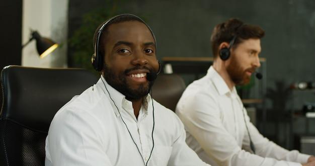 Retrato del hombre joven afroamericano hermoso en auriculares que trabaja en la computadora en centro de atención telefónica.