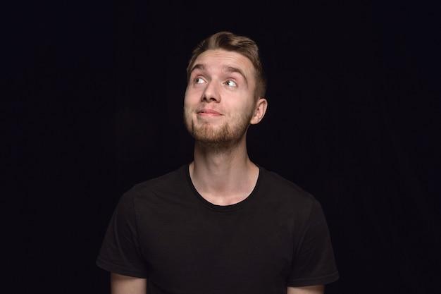 Retrato de hombre joven aislado sobre fondo negro de estudio de cerca. photoshot de emociones reales del modelo masculino. soñando y sonriendo, esperanzado y feliz. expresión facial, concepto de emociones humanas.