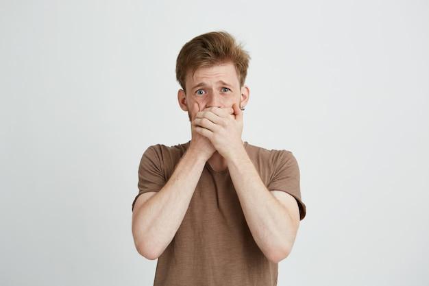 Retrato de hombre joven asustado asustado sorprendido cerrando la boca con las manos.