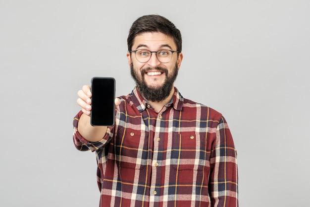Retrato de hombre joven atractivo que presenta smartphone para publicidad