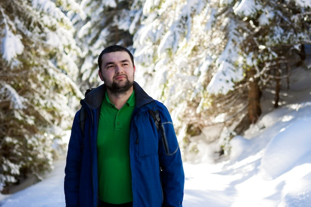 Retrato de hombre joven con barba guapo en bosque de invierno