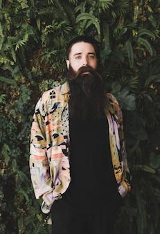 Retrato de un hombre joven con barba larga mirando a cámara