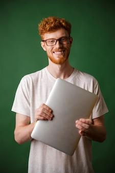 Un retrato de hombre joven barbudo de cabeza lectora en camiseta blanca con laptop
