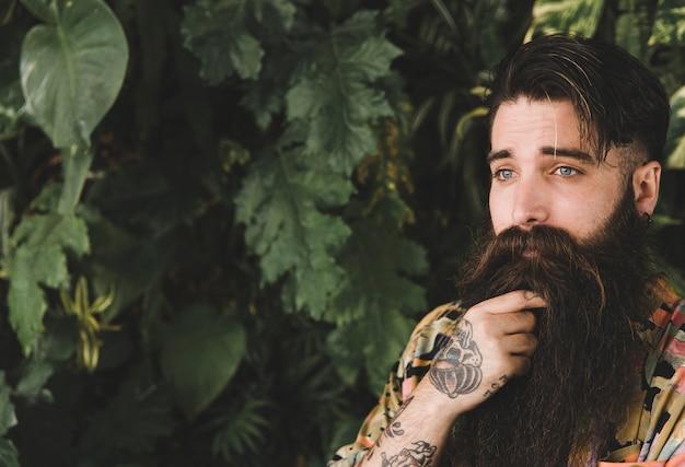 Retrato de un hombre joven barbudo de pie delante de las hojas