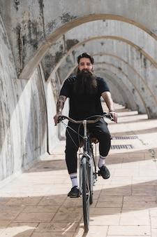Retrato de un hombre joven barbudo que monta la bicicleta en arcos