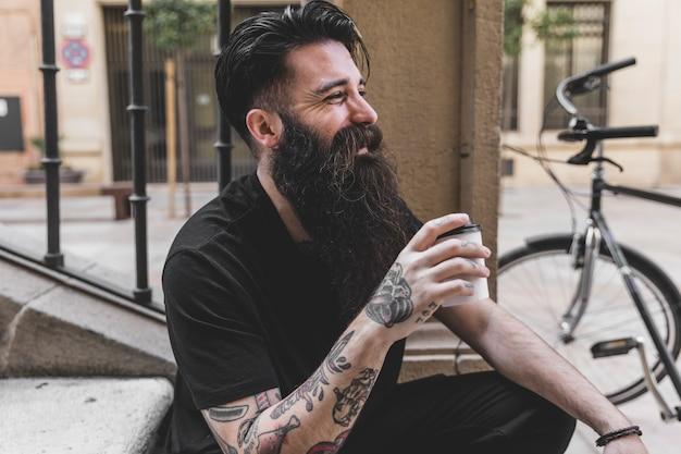 Retrato de un hombre joven barbudo que se sienta en la escalera que sostiene la taza de café