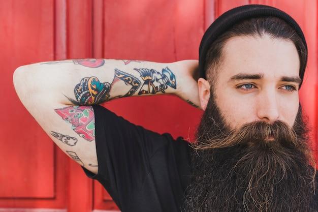 Retrato de un hombre joven barbudo con tatuaje colorido en su mano contra el telón de fondo rojo