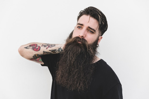 Retrato de hombre joven barbudo con tatuaje en su mano mirando a otro lado sobre fondo blanco