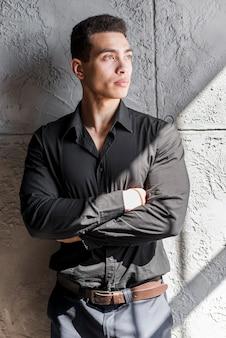 Retrato de un hombre joven con los brazos cruzados de pie contra la pared gris
