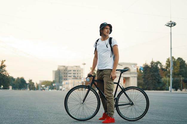 Retrato de hombre joven caminando con bicicleta cuidadosamente clásica en calles de la ciudad