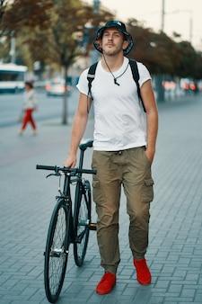 Retrato de hombre joven caminando con bicicleta cuidadosamente clásica