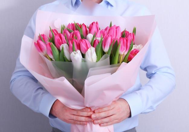Retrato de un hombre joven en camisa azul con ramo de tulipanes rosados y blancos en gris. tarjeta de felicitación de primavera. pascua, concepto de flor de primavera. día de la madre o de la mujer.