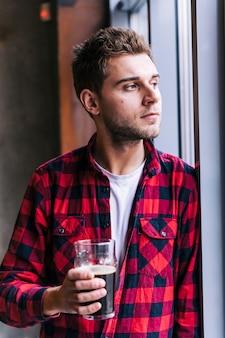 Retrato de un hombre joven en la camisa a cuadros roja del modelo que sostiene el vidrio de cerveza