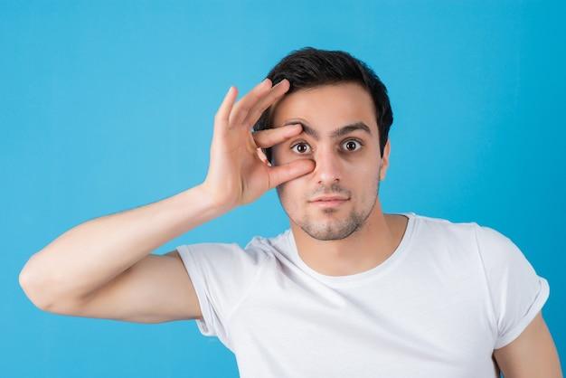 Retrato de hombre joven en camiseta blanca haciendo ojos binoculares en la pared azul
