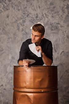 Retrato de hombre joven con cartas de juego de barril. chico guapo muestra trucos con tarjeta. manos inteligentes de mago