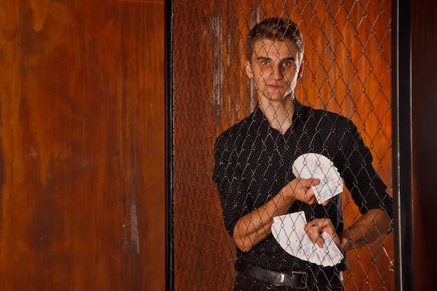 Retrato de hombre joven con cartas de juego en la puerta. chico guapo muestra trucos con tarjeta. manos inteligentes de mago