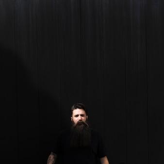 Retrato de un hombre joven contra el fondo negro