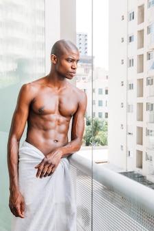 Retrato de un hombre joven descamisado afro que se coloca en el balcón que mira hacia fuera