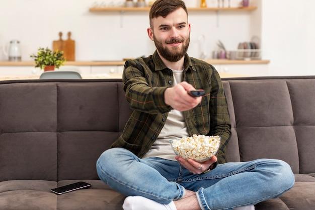 Retrato de hombre joven disfrutando de descanso de tv