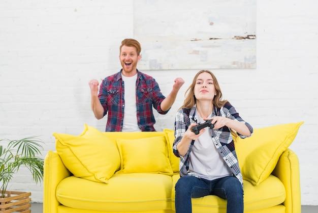 Retrato de un hombre joven emocionado de pie detrás de la mujer jugando videojuegos en casa