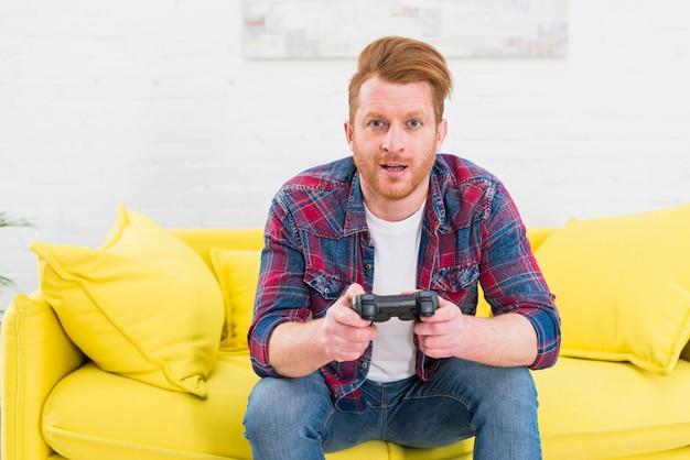 Retrato de un hombre joven emocionado que se sienta en el sofá amarillo que juega al videojuego