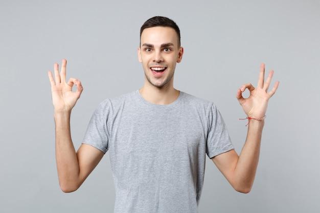 Retrato de hombre joven emocionado en ropa casual tomados de la mano en gesto de yoga meditando relajante