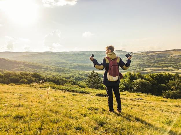 Retrato de hombre joven con equipo de fotografía y manos levantadas caminando en el campo de montaña