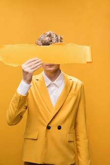 Retrato de hombre joven en un escenario amarillo con papel tirado enfrente de la cara