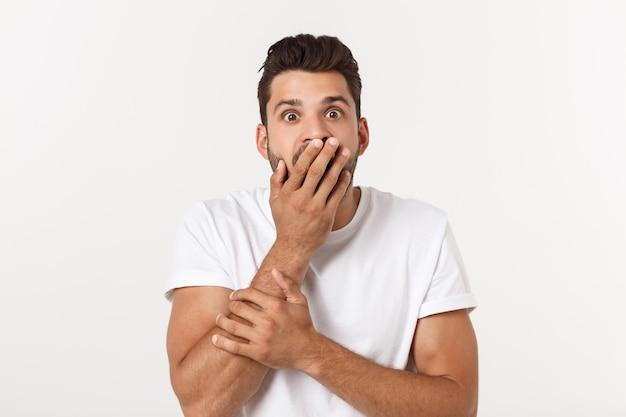 Retrato del hombre joven con la expresión facial chocada, aislado sobre blanco.