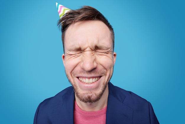 Retrato de hombre joven expresivo con sombrero de cumpleaños
