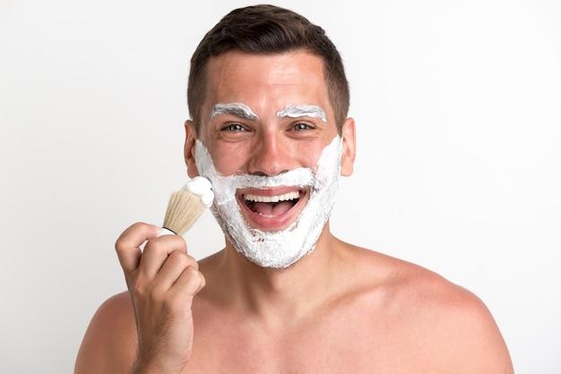 Retrato de hombre joven feliz aplicando espuma de afeitar sobre fondo blanco.