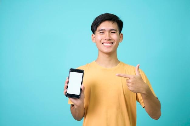 Retrato de hombre joven feliz apuntando a la pantalla en blanco en el teléfono inteligente.