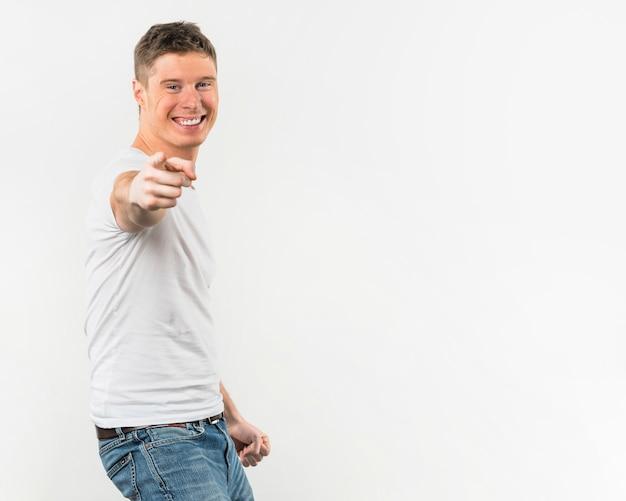 Retrato de un hombre joven feliz que señala su dedo hacia la cámara de pie contra el fondo blanco