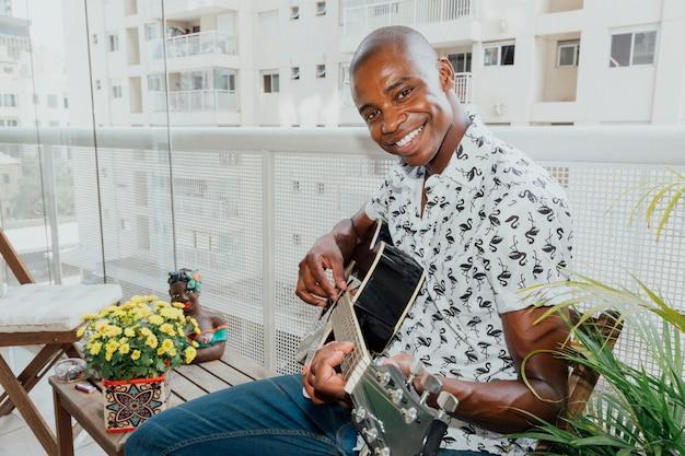 Retrato de un hombre joven feliz que se sienta en el balcón que toca la guitarra que mira la cámara