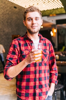 Retrato de un hombre joven feliz que sostiene el vidrio de cerveza que mira la cámara