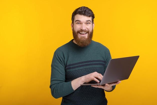 Retrato de hombre joven feliz usando laptop mientras está de pie sobre la pared amarilla