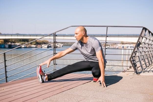 Retrato de hombre joven en forma estirando la pierna en el puente cerca del lago