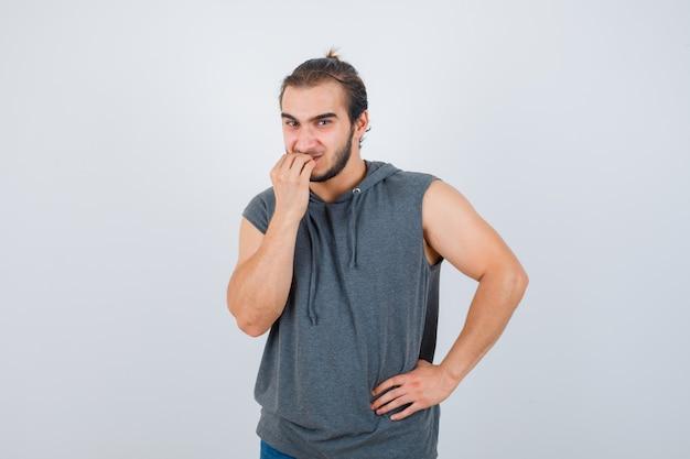 Retrato de hombre joven en forma mordiendo las uñas en sudadera con capucha sin mangas y mirando estresado vista frontal
