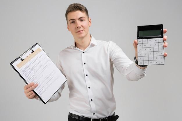 Retrato de hombre joven con forma de pago de facturas y calculadora en sus manos aisladas en blanco