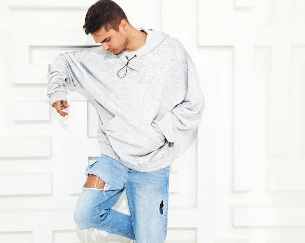 Retrato de hombre joven y guapo modelo vestido con ropa casual gris con capucha posando cerca de la pared blanca con textura