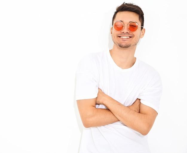 Retrato de hombre joven y guapo modelo vestido con ropa de jeans y camiseta en gafas de sol posando. brazos cruzados