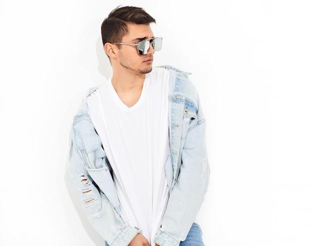 Retrato de hombre joven y guapo modelo vestido con ropa de jeans en gafas de sol posando. aislado